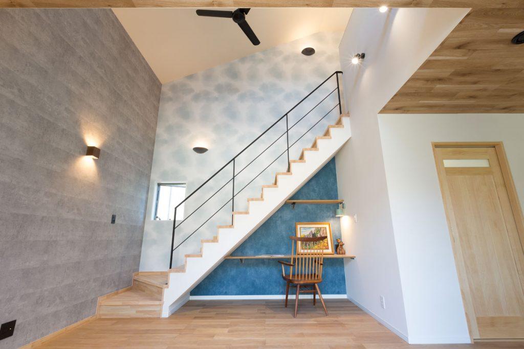 コンクリート調や滲みをイメージしたクロス使いが映えるリビング。階段下にはアクセントのブルーをあしらった子どもの勉強スペースを。